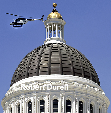 THE DOME ---It is unusual to see a police helicopter flying so low and so close to the Capitol dome, but this day protesters were clashing with police over production of genetically-modified food. Even with so much going on down below, my attention was drawn upward to the majestic dome, the blue sky and what seemed like the building's protector.