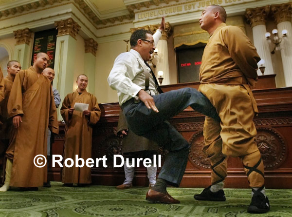 THE KICK --- I was in the Capitol for another assignment when a legislative staffer suggested I head to the Assembly floor.  The Assembly was not in session but a group of Shaolin Monks from Hunan province in China was getting a special tour. As I prepared to leave after 10 minutes of hum-drum photos, I heard the group's translator encourage Wesson to kick one the Monks in the crotch, a method they use to toughen themselves.  As Wesson approached the monk, I quickly dropped to the floor and stayed underneath a desk for a low angle shot. Wesson kicked three times, the monk never flinched, and I had one of my most memorable photos from a decade under the dome. 